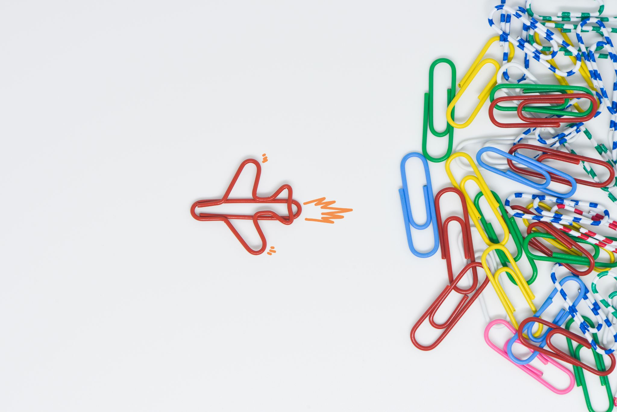 Paperclips in all different colours like red, blue, pink, green, yellow and striped. One red paperclip is formed into a plane and is flying away from the other paperclips