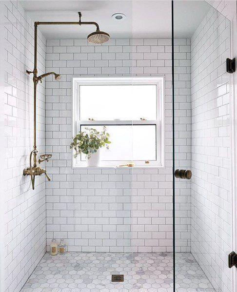 Banheiro com revestimento subway branco nas paredes, piso em formato hexagonal pequeno branco, box de vidro e chuveiro dourado.