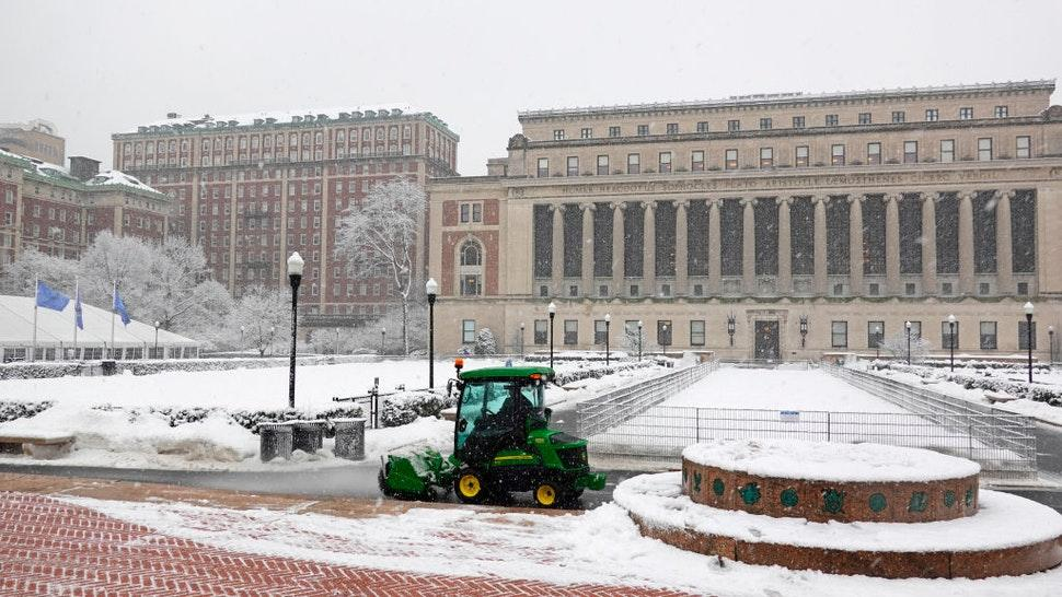 Tractor with roller brush and blower removing snow from walkways on the Columbia University campus area in New York.