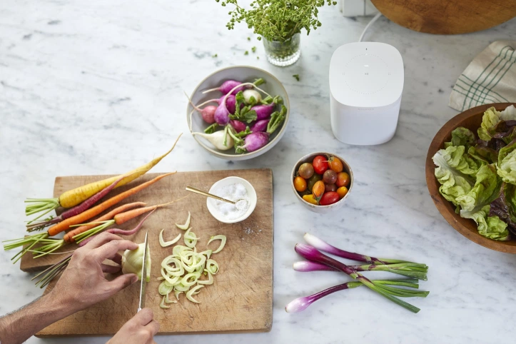 Sonos One on a kitchen table top while a person cuts vegetables