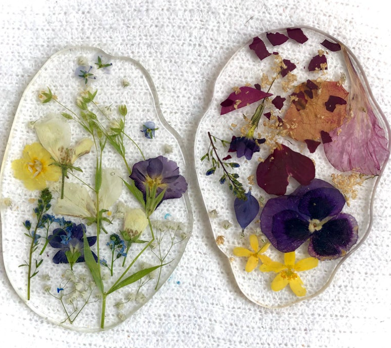 two resin coasters with pressed flowers on white fabric background