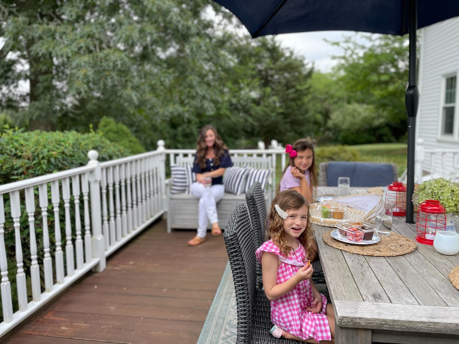 Little girls enjoying snacks on the deck yard protected by Modern Pest