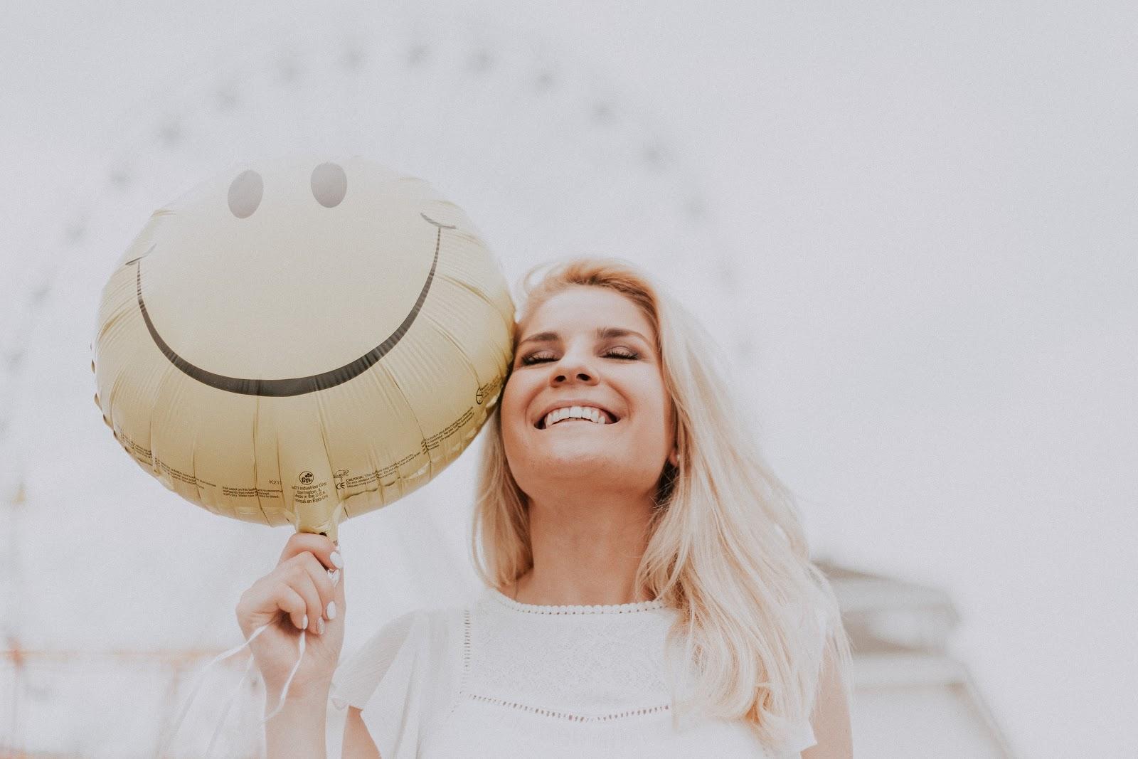 Woman holding up a smiley-face balloon.