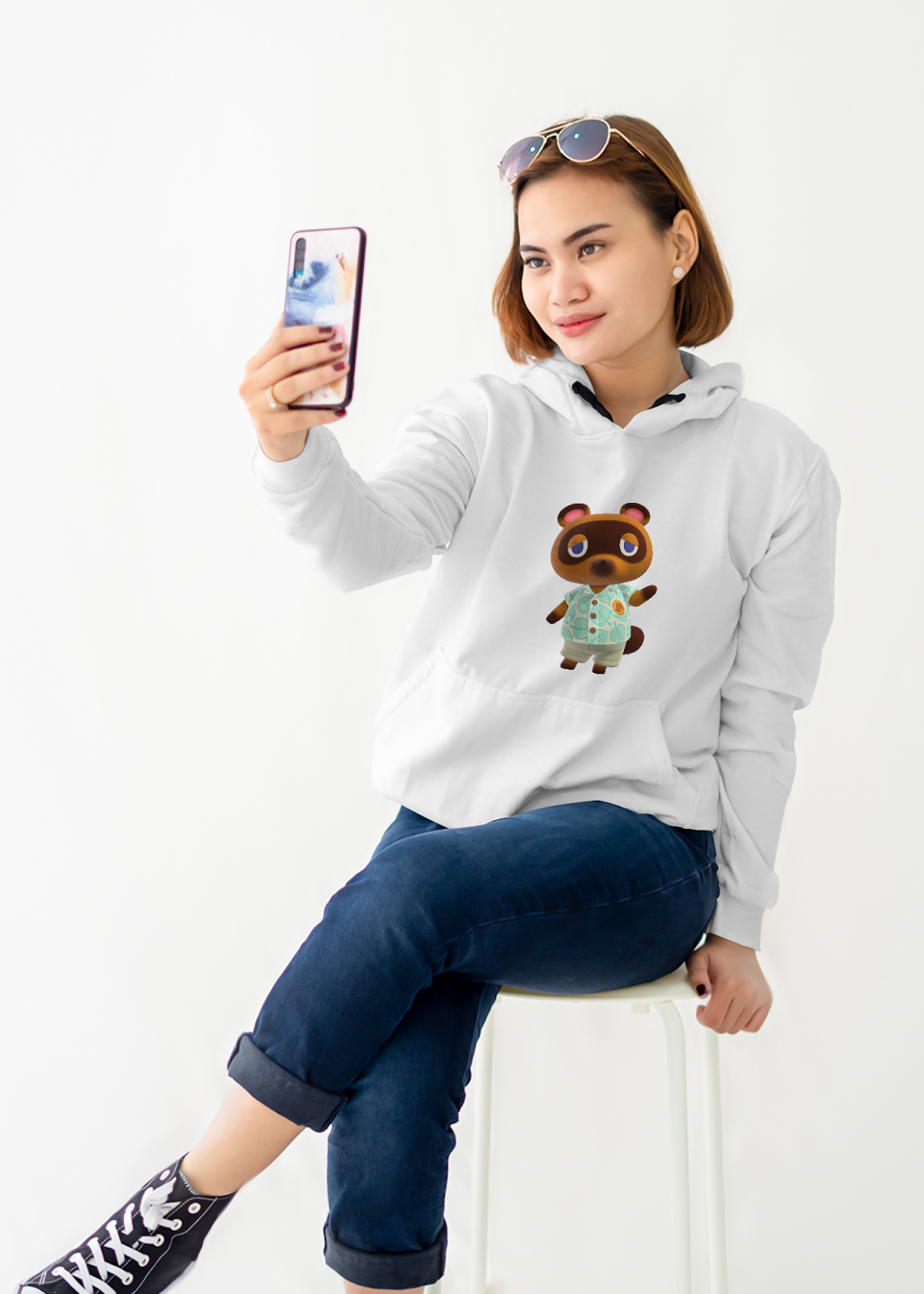 Sweater mockup featuring a woman holding her phone and taking a selfie