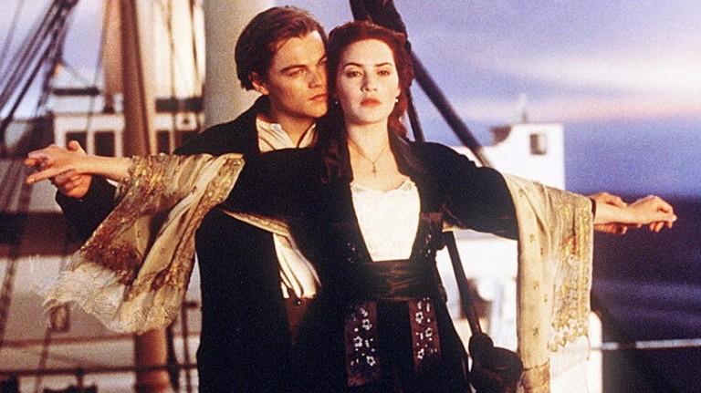 Cena de homem segurando braços abertos de uma mulher em um navio .