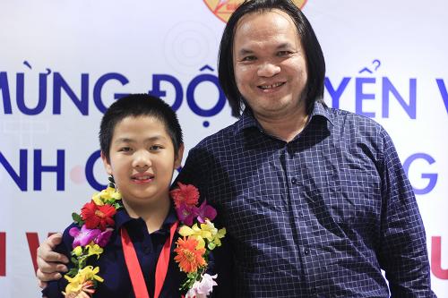 Trịnh Anh Minh cùng thầy giáo Trần Phương trong buổi lễ chúc mừng thành tích của đoàn Việt Nam tại sân bay Nội Bài tối 4/10. Ảnh:Dương Tâm