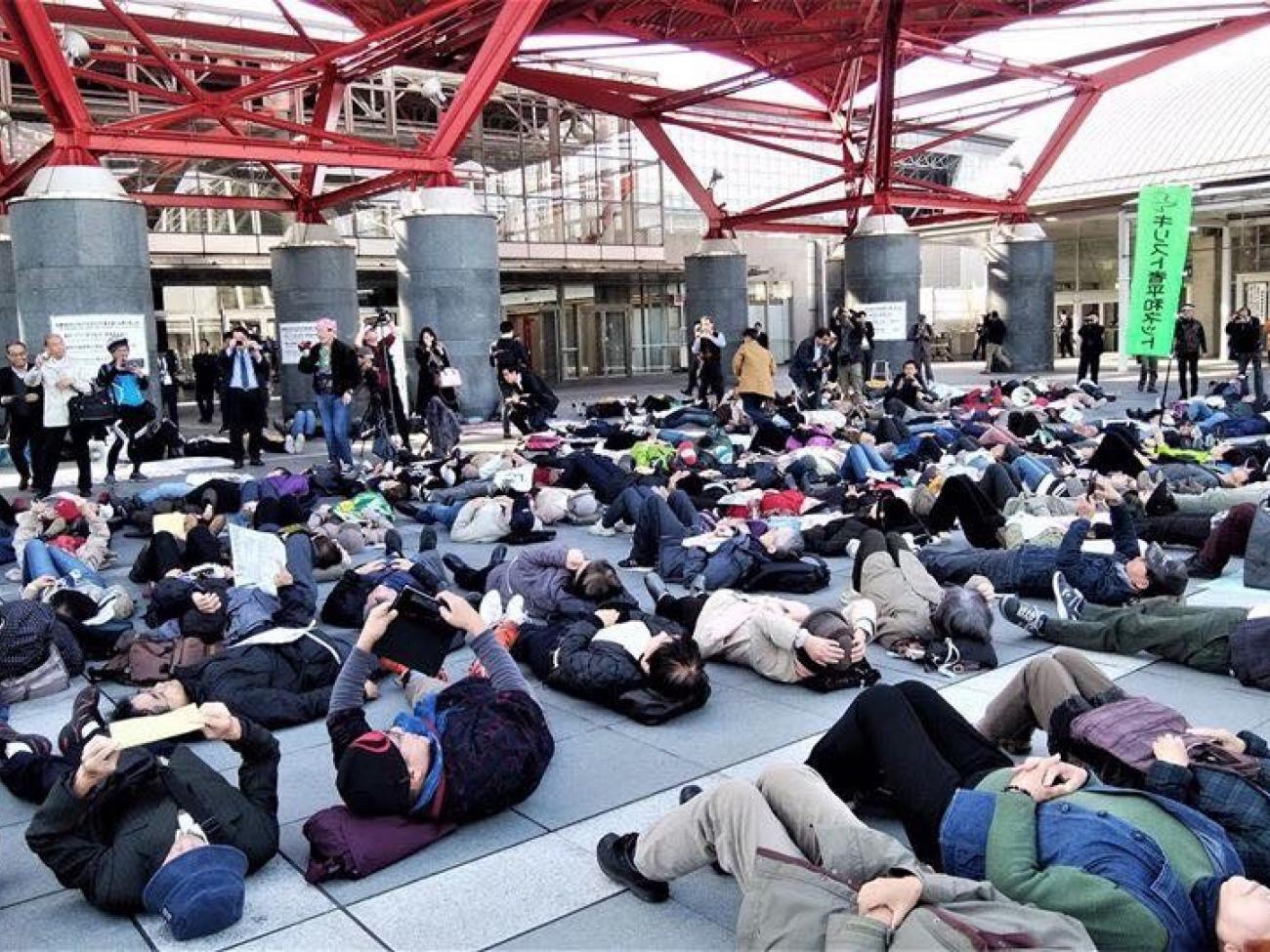 Activists stage a die-in outside the Japan DSEI arms fair, Chiba