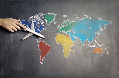 Top view of crop anonymous person holding toy airplane on colorful world map drawn on chalkboard