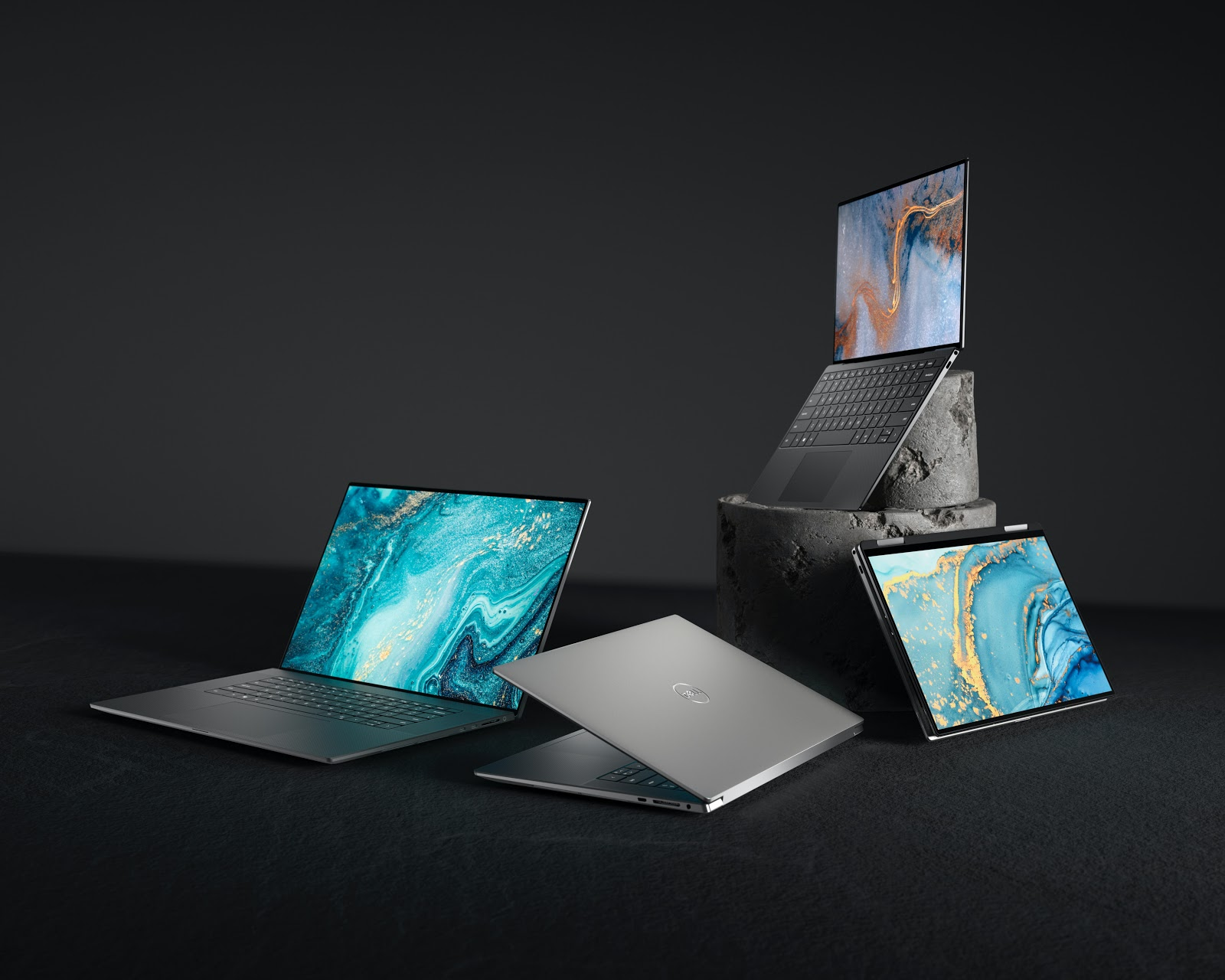 open laptops with marble screen savers on a black background