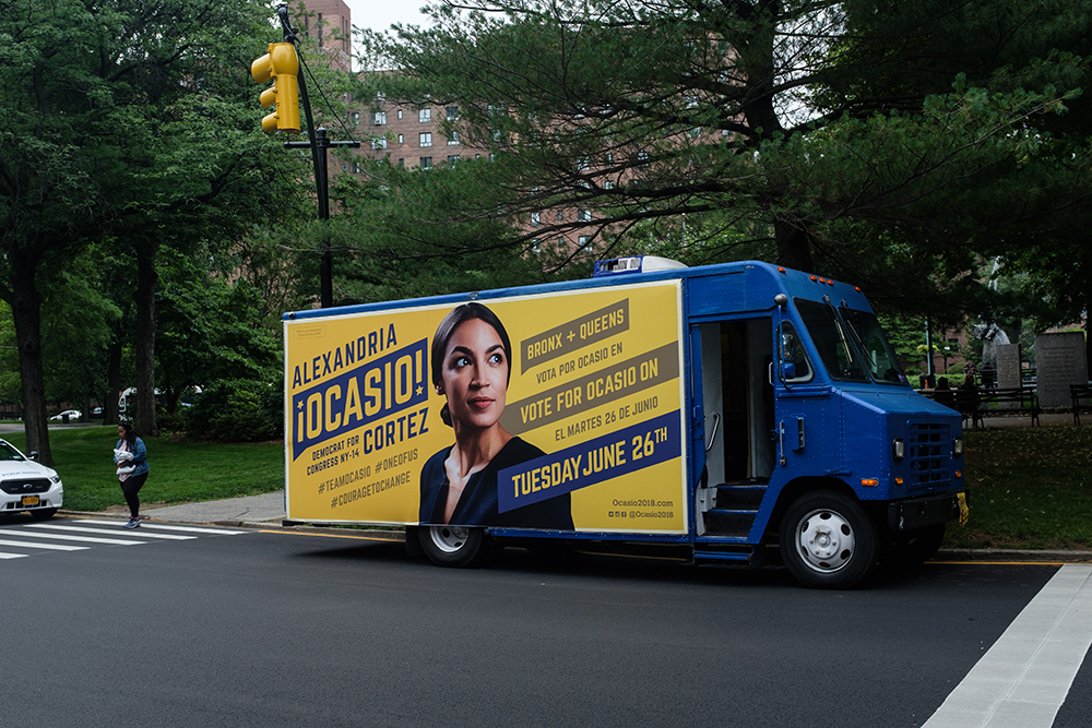Alexandrio Ocasio-Cortez truck-side ad with the colors blue and yellow