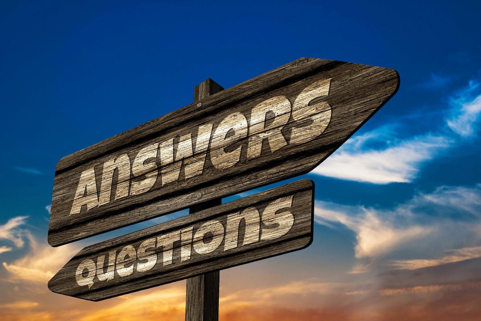 Drogowskaz na tle nieba, wskazuje pytania i odpowiedzi.