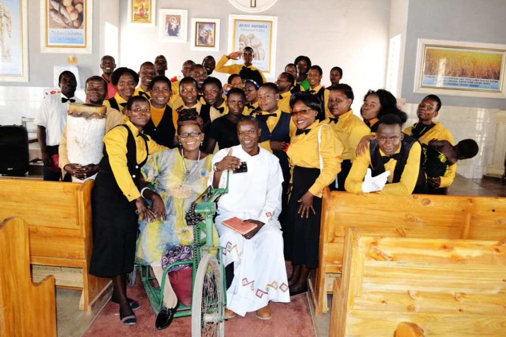 Second image of the community with lady Mayimayi in her wheelchair with the choir and the parish priest seated to her left. Everybody smiling.