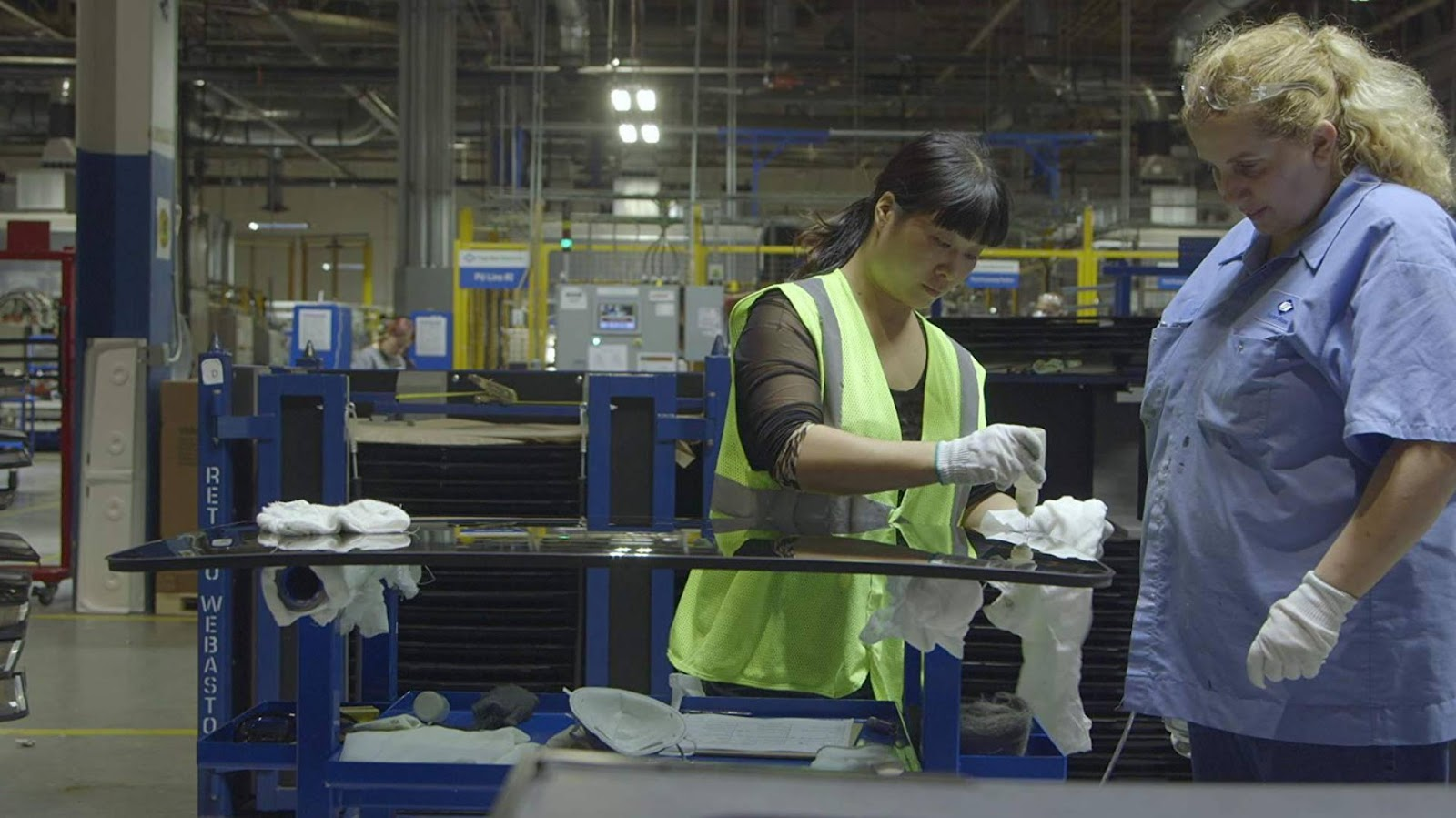 duas mulheres operando uma máquina têxtil dentro de uma fábrica