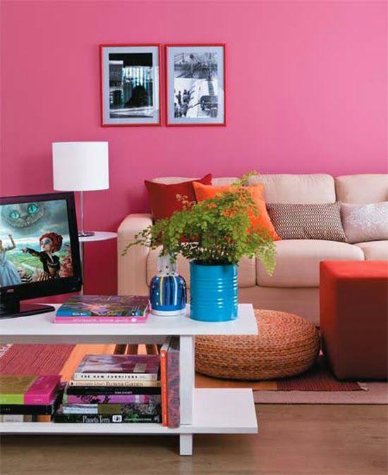Sala com ambiente colorido, parede rosa, sofá branco com almofadas coloridas, vaso de planta azul e puff laranja.