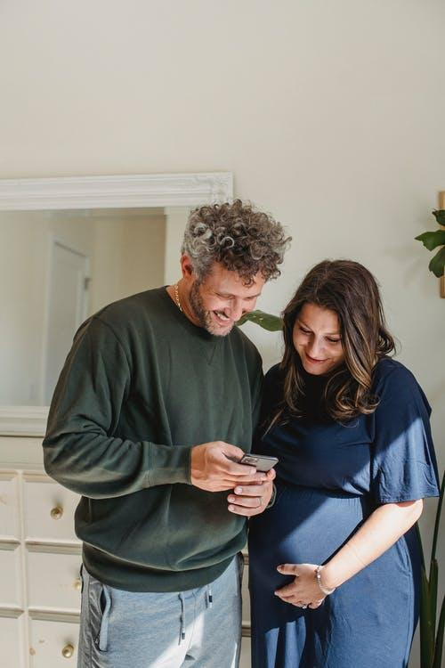 Cheerful adult male in casual clothes smiling and showing video on smartphone to smiling pregnant wife standing in light room on sunny day