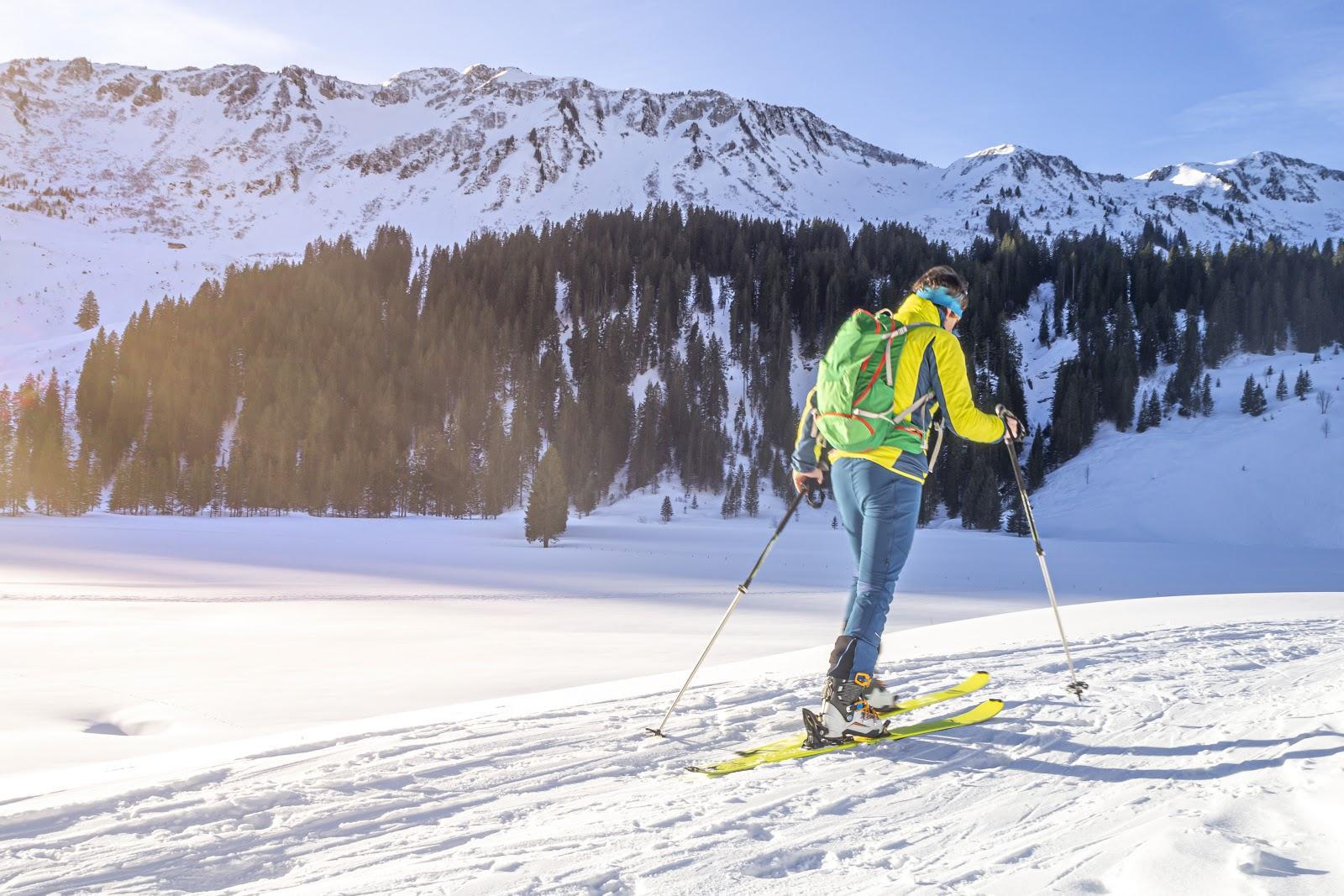 Esquiador de montaña ascendiendo por las pistas