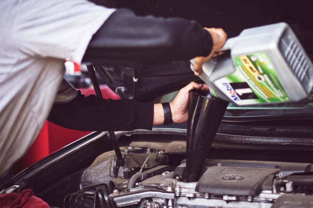 Un meccanico che sta mettendo dell'olio all'interno di un motore di un auto