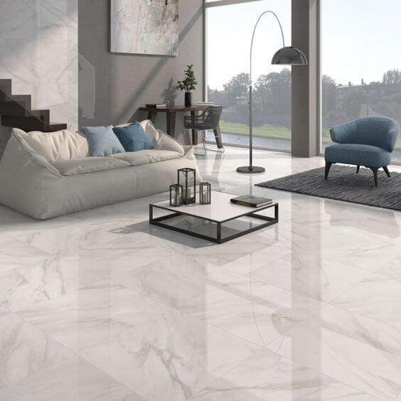 Sala com piso porcelanato marmorizado branco com sofá puff branco com almofada coloridas, poltrona azul, parede cinza e parede de fundo envidraçada.