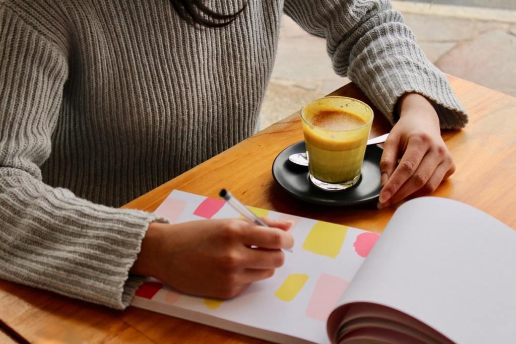 Pessoa escrevendo em um caderno sobre seu planejamento financeiro pessoal