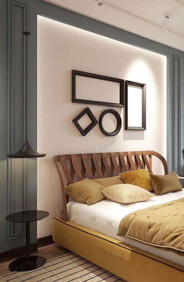 Cama com cabeceira de design diferenciado, parede branca de fundo com moldura cinza.