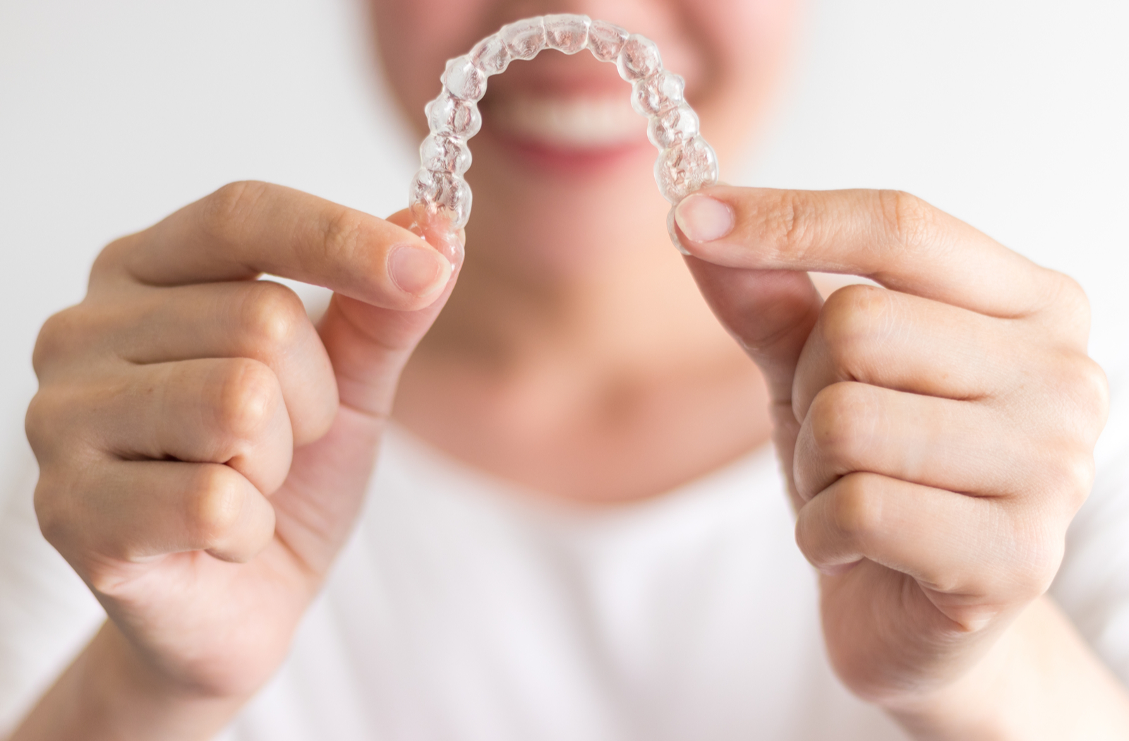 lady smiling out of focus holding a clear plastic aligner with both hands