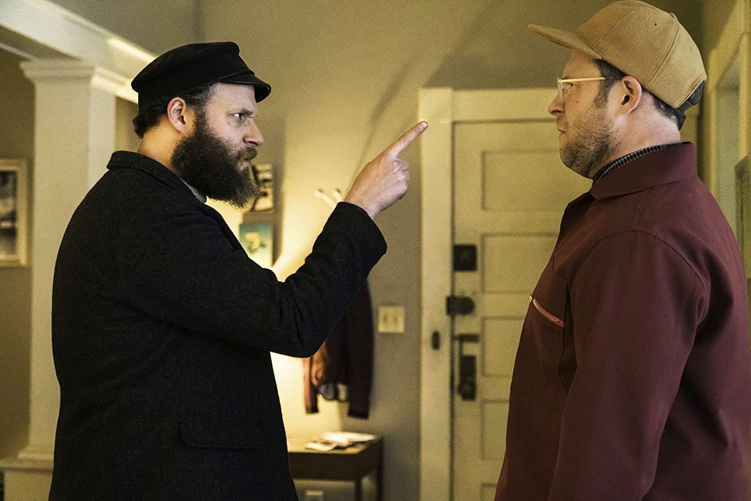 Seth Rogen in An American Pickle (2020). Left is Herschel, a Jewish man from the early 1900s, wearing a thick black overcoat and black cap, with a thick beard. He has a severe expression and points his finger in the face of Ben (also Rogen), an identical man but dressed in a modern burgundy jacket and beige snapback cap. He is looking confused.