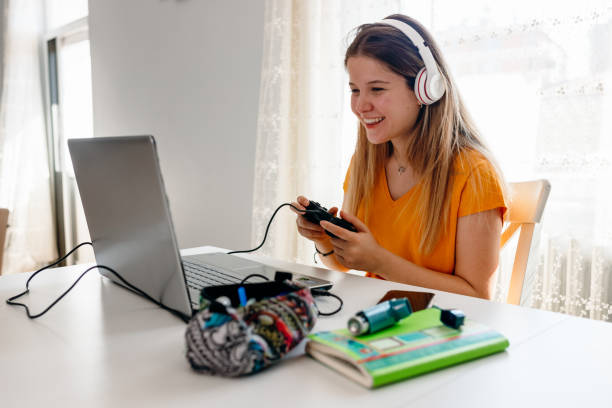 college girl takes a break college girl takes a break laptop gaming stock pictures, royalty-free photos & images