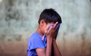 A boy holding his hands to his face.