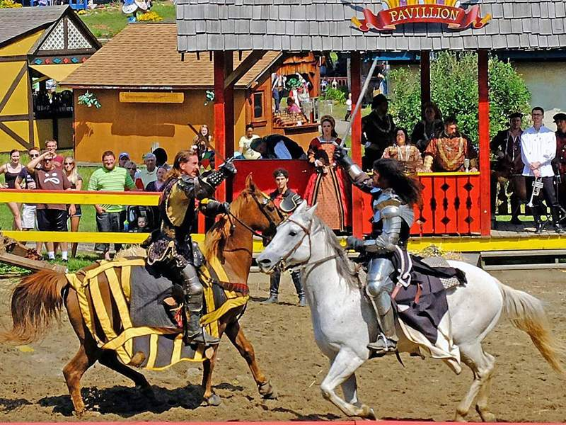 two men in knight costumes battling with swords on horses at a renaissance festival