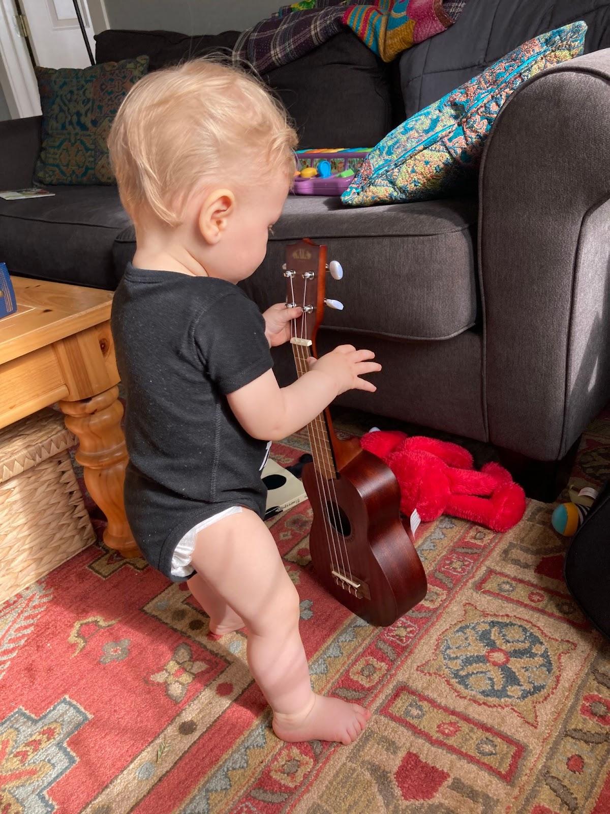 Baby holding ukulele