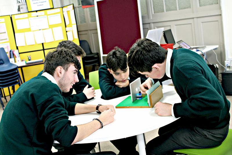 Пятеро мальчиков в зеленых свитерах строят модель