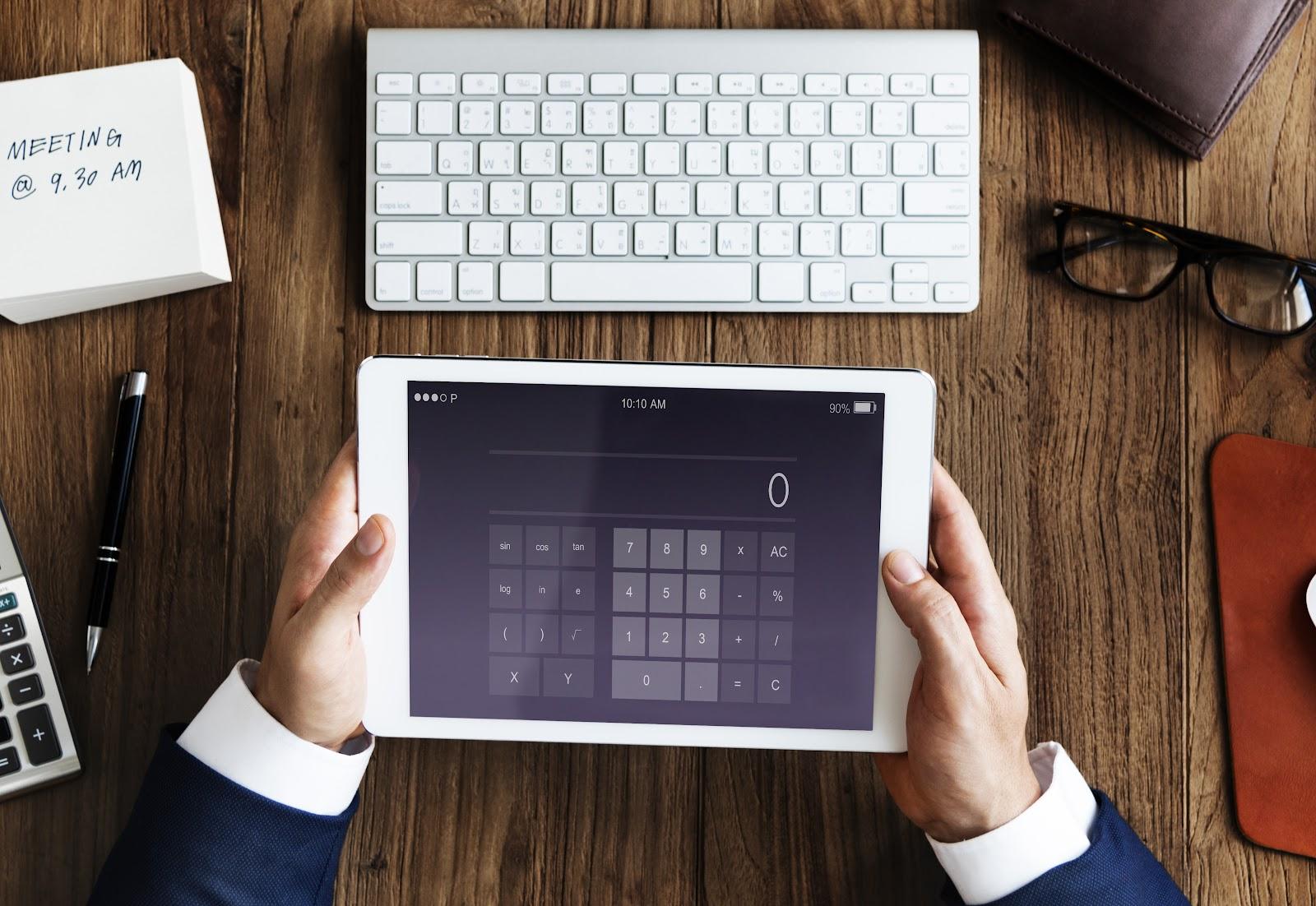 Uma mão segurando um tablet com a tela de uma calculadora.
