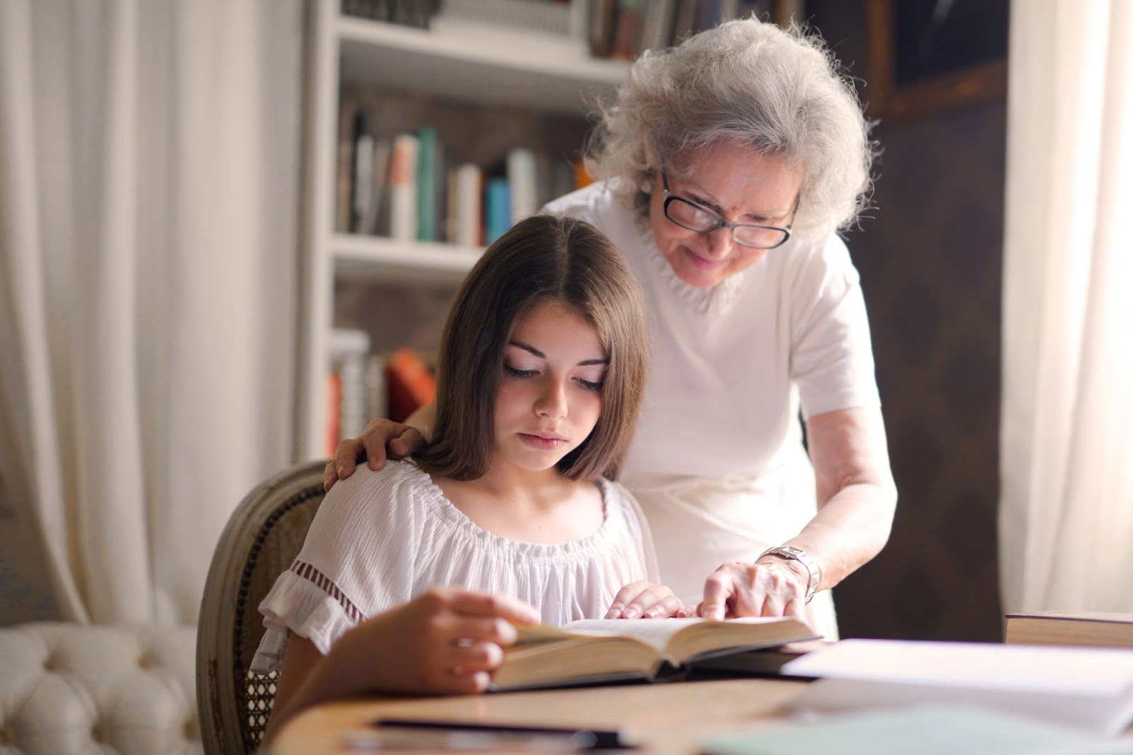 Young girl reading book with senior woman helping her