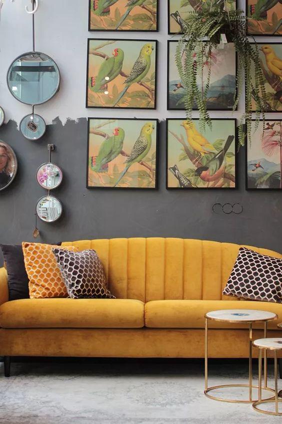 Sala com sofá amarelo, parede cinza e quadros decorativos em tons amarelo e cinza.