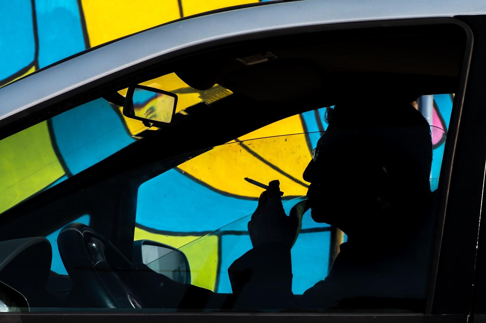 Um homem fumando dentro do carro.