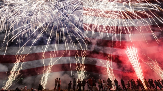 A US flag behind a backdrop of fireworks.