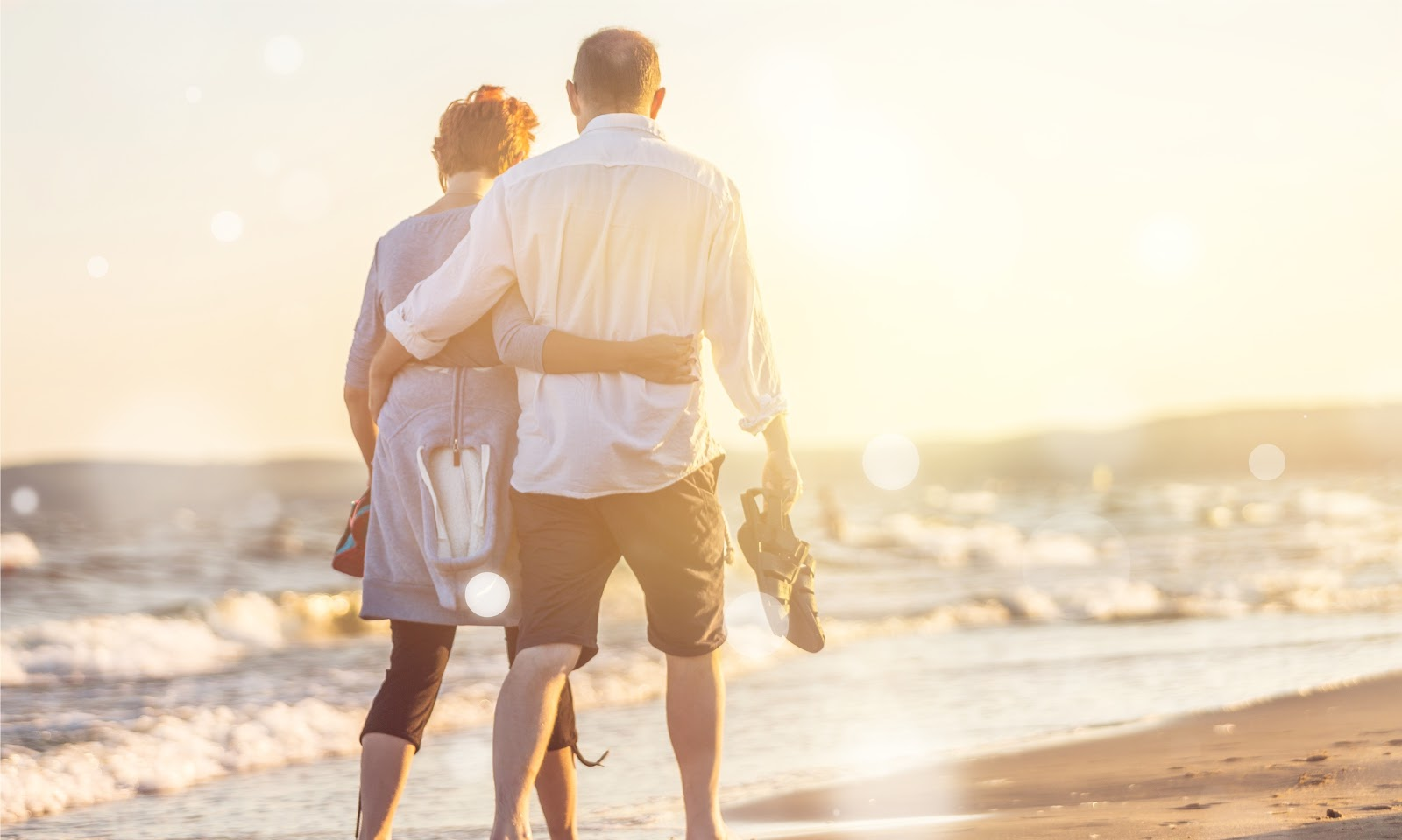 Elderly couple walking and hugging each other while on the seashore