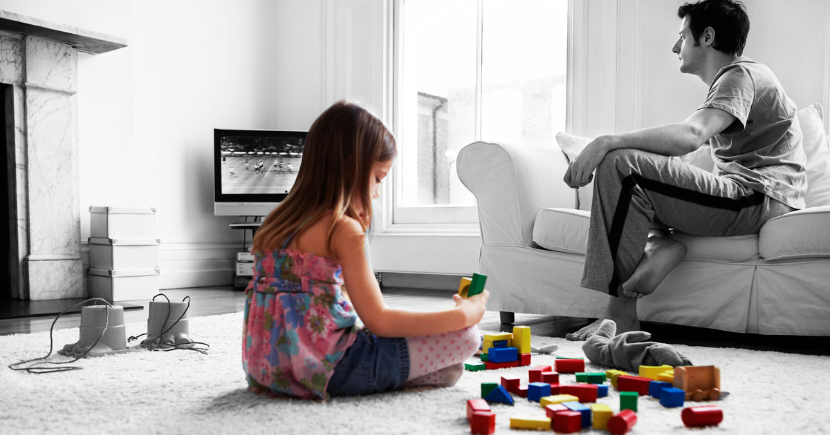 Girl Playing while Dad Watches Television