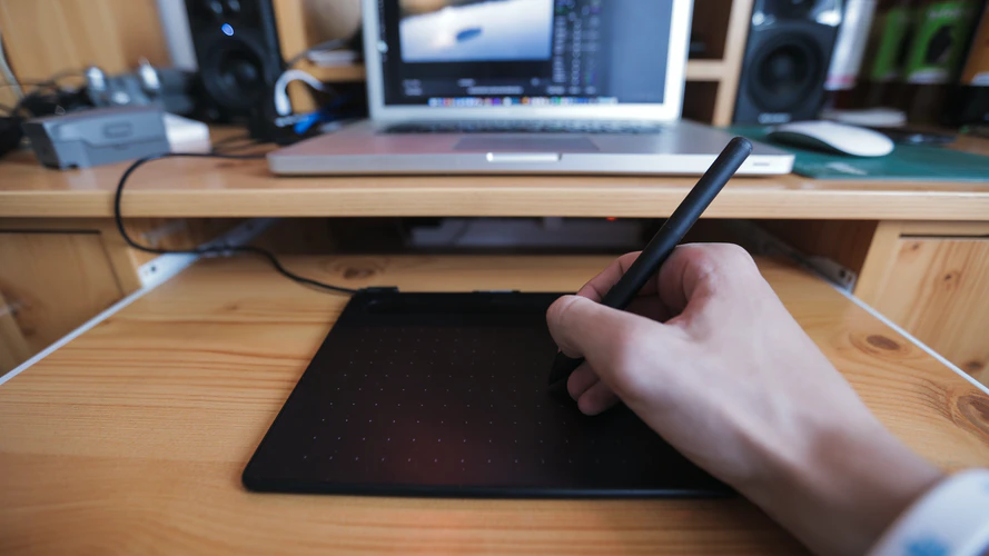 a man's hand on a drawing tablet