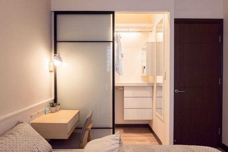 床的左側使用梣木床頭櫃與小植栽右側則使用系統櫃設計出不落地床邊桌