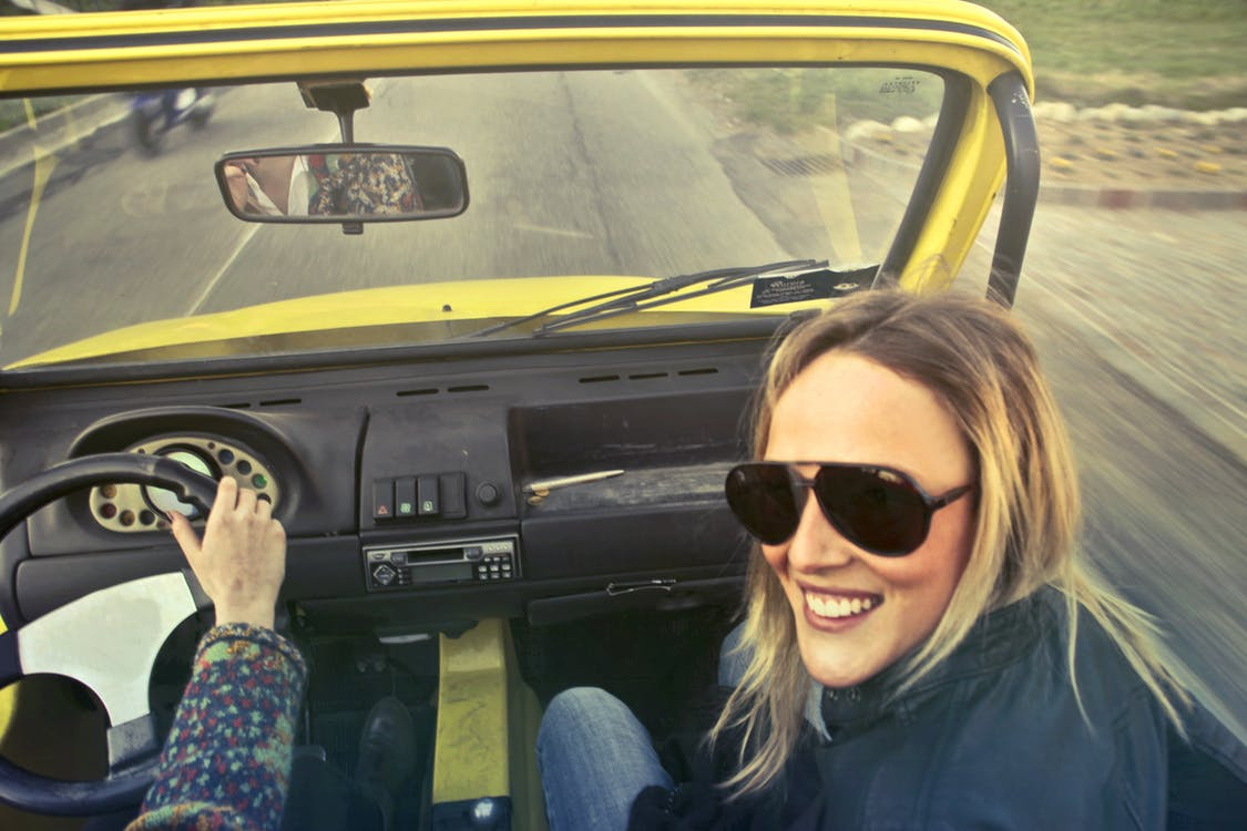 Woman In Black Aviator Sunglasses Sitting On Car's Passenger Seat