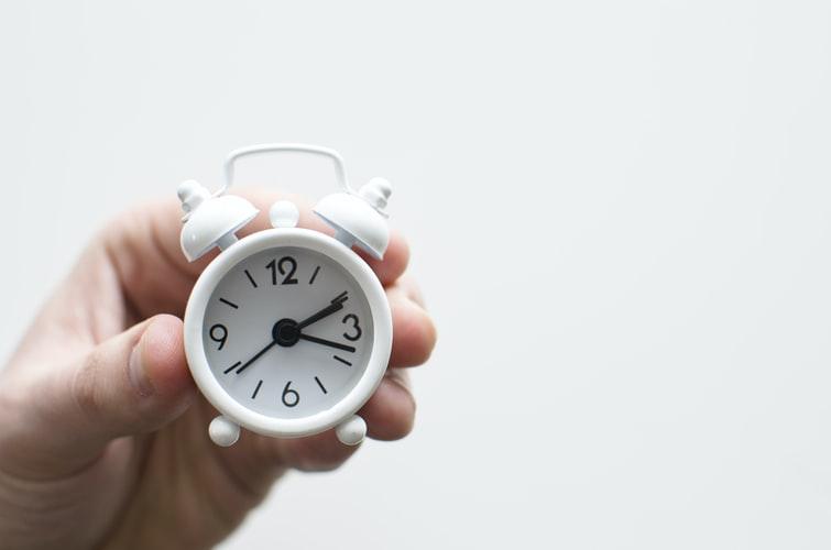human hand holding small clock