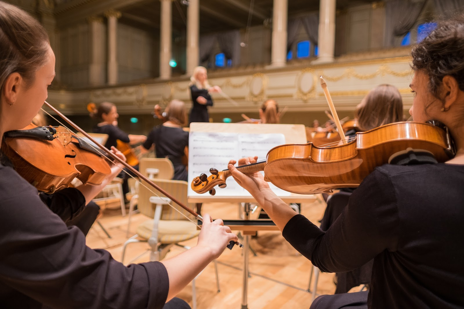 photo of a group of musicians with two violinists in the foreground
