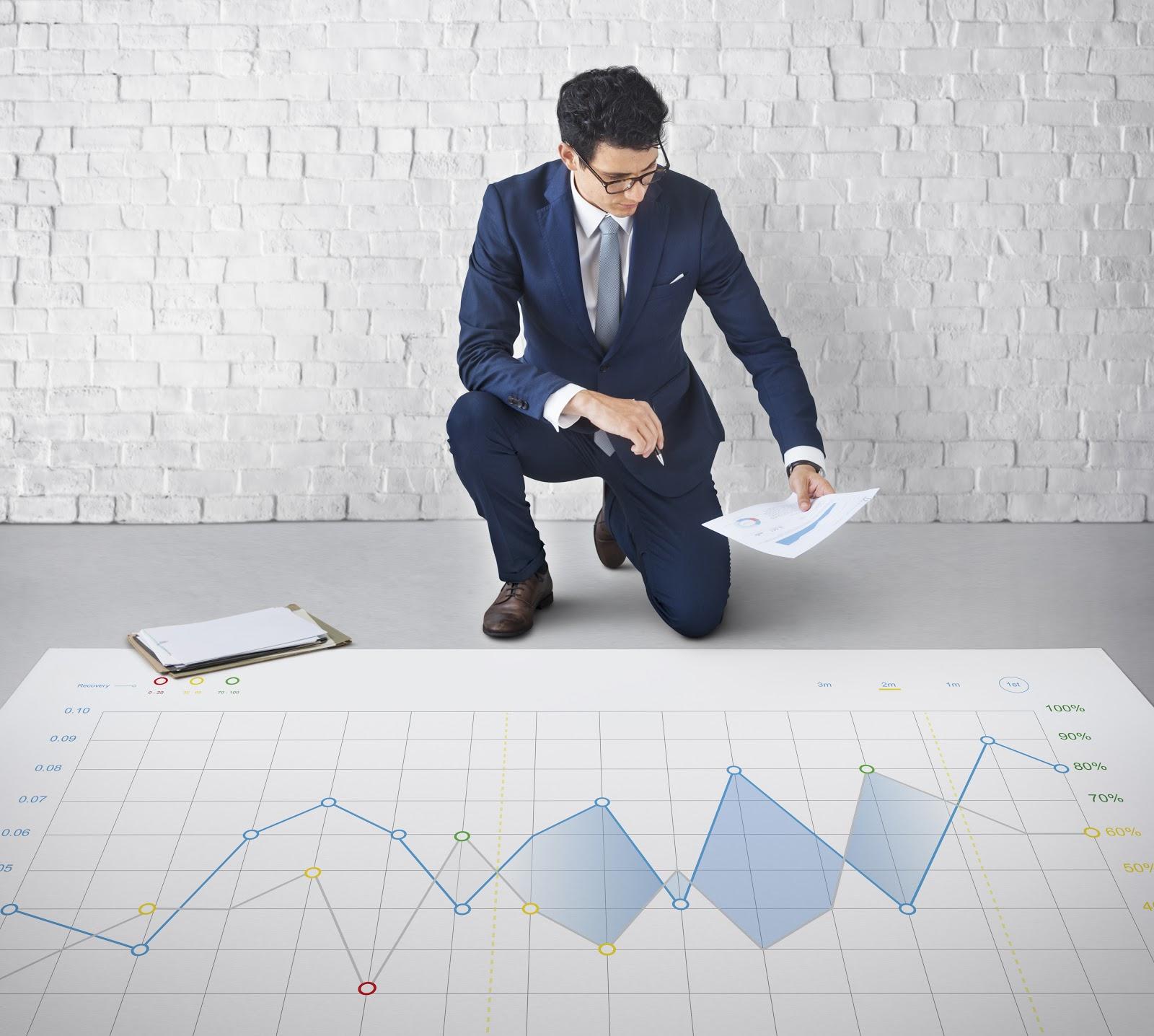 Um homem olhando para um papel para conferir um gráfico posto ao chão.