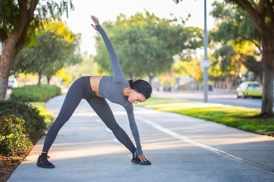 Mulher se alongando antes de praticar exercício físico.