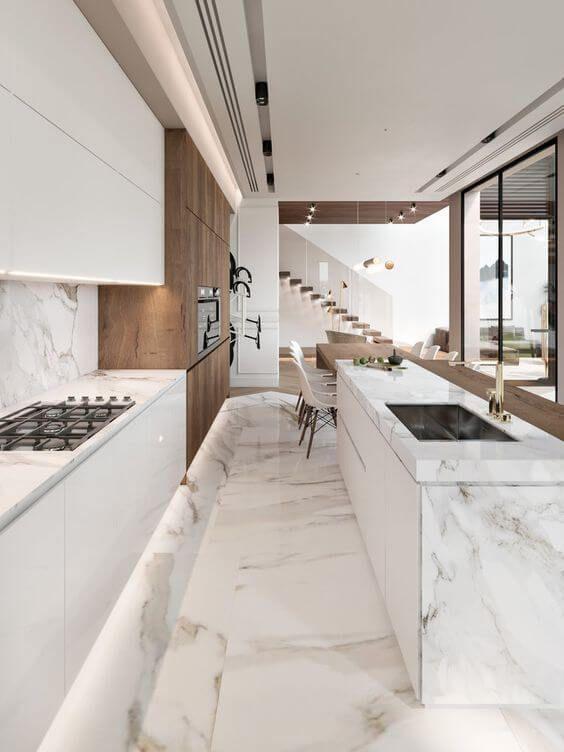 Cozinha com revestimento marmorizado na parede da pia, bancada e piso, armário amadeirado e branco e portas de vidros.