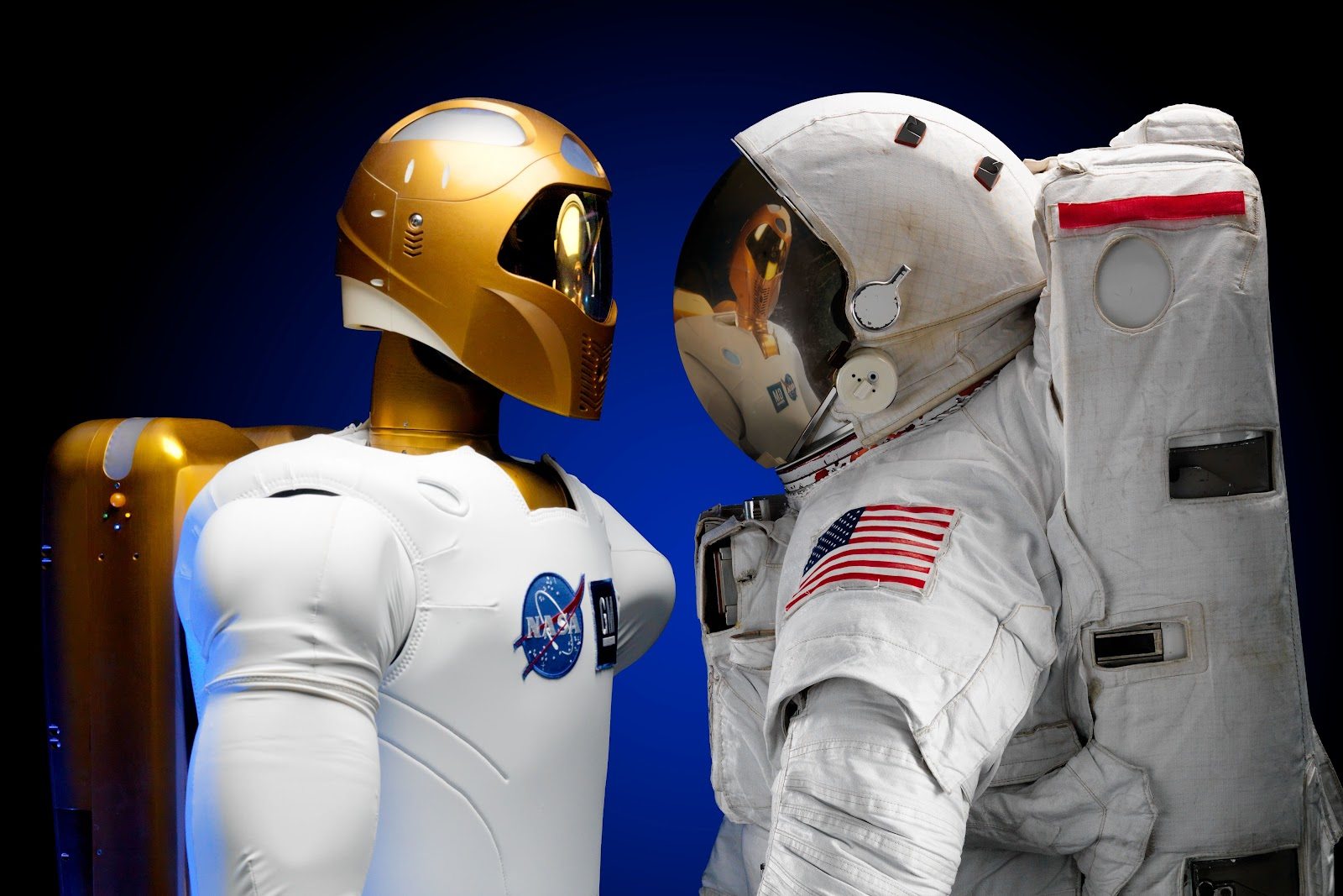 A robot in front of an astronaut, the robot has a NASA logo in its chest