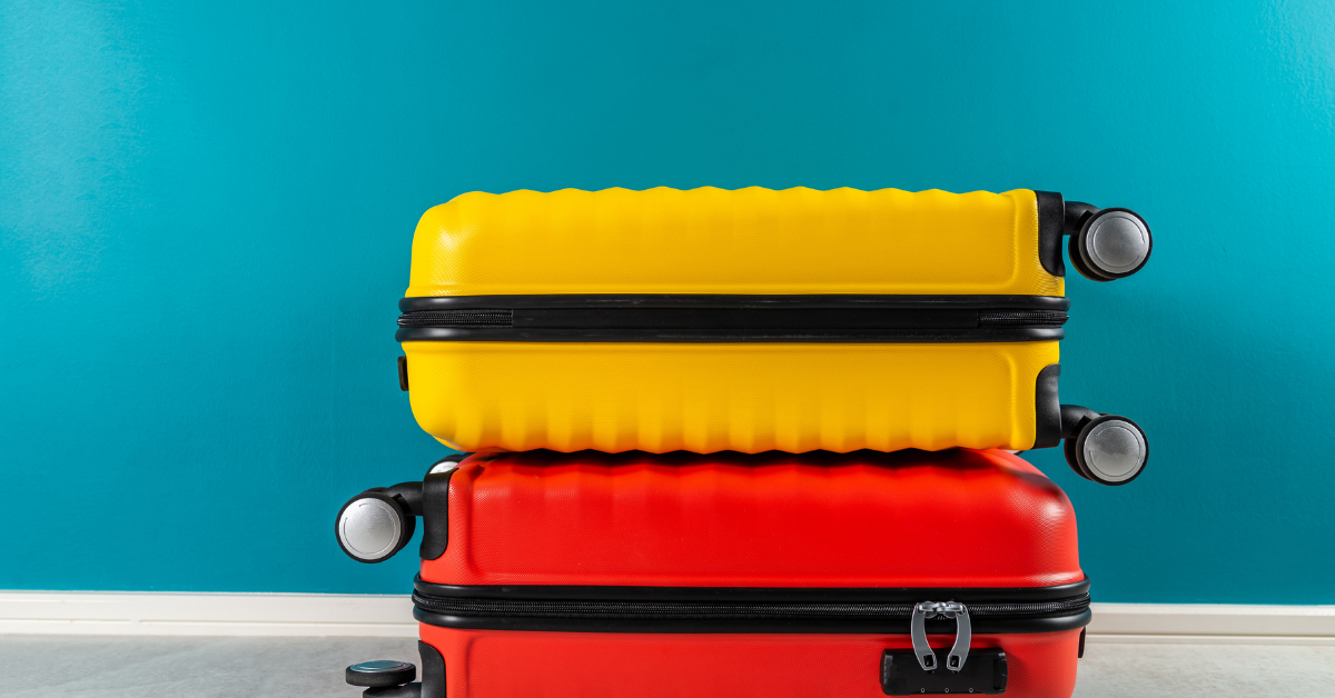 A yellow carry on on top of a red carry on