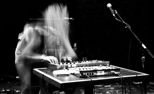 Black and white photo of a blurred performer who stands behind a synthesizer. Photo illustrates motion blur from the camera lens.