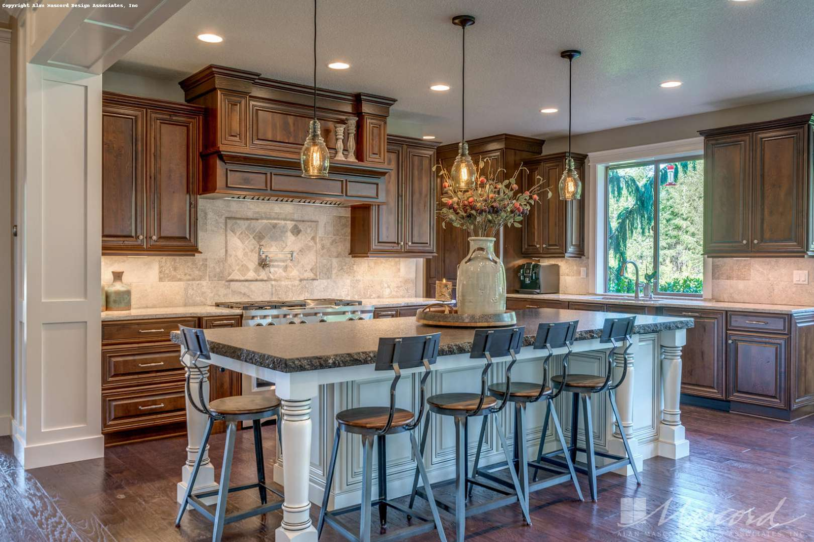 antique brown kitchen cabinets with an antique white island, pendant lighting and tile backsplash